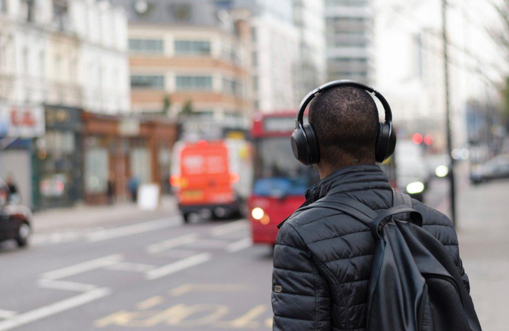Un homme écoutant un podcast pendant qu'il marche dans la rue